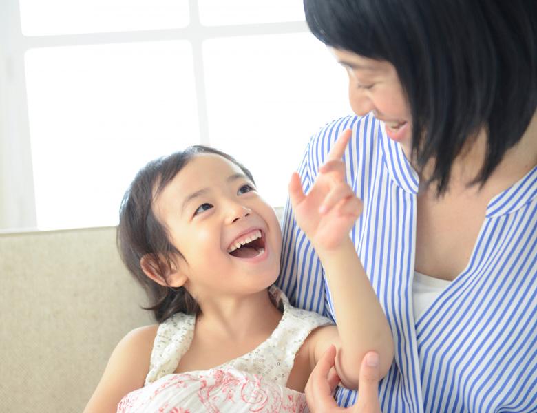 笑顔で会話する女の子と母親の写真